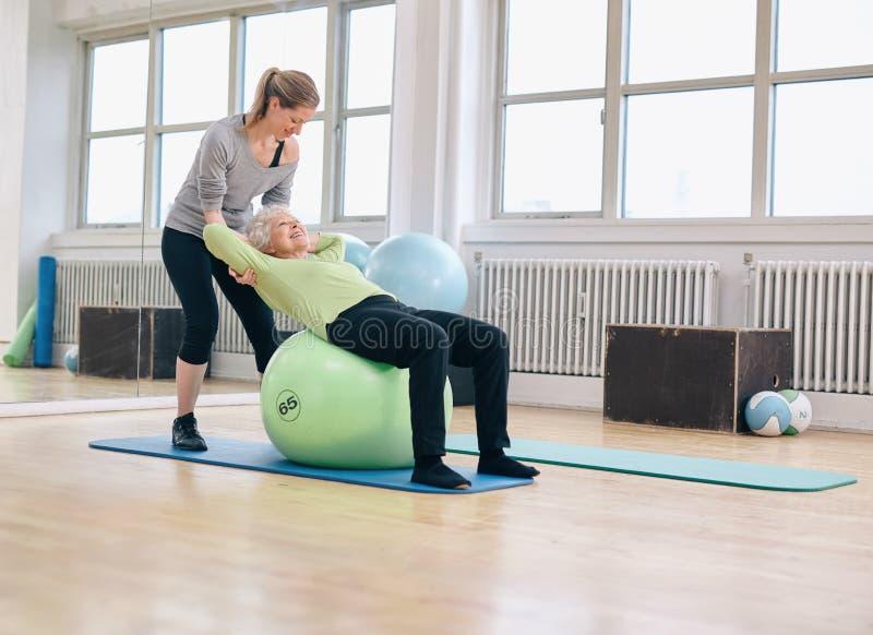 Coche femenino que ayuda a la mujer mayor que ejercita en gimnasio imágenes de archivo libres de regalías