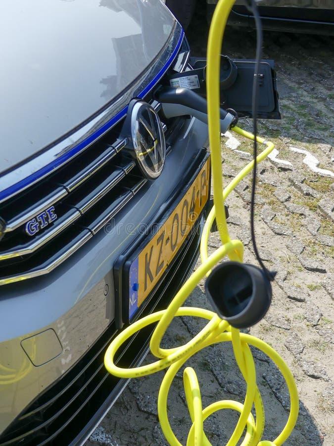 Coche hybric eléctrico de VW que carga en la estación del enchufe adentro imagenes de archivo