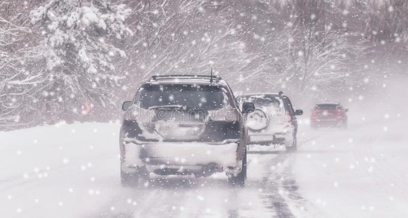 Coche móvil en el camino nevoso del invierno entre bosque congelado después del aguanieve Tiempo frío, nevada, mala visibilidad,  fotos de archivo