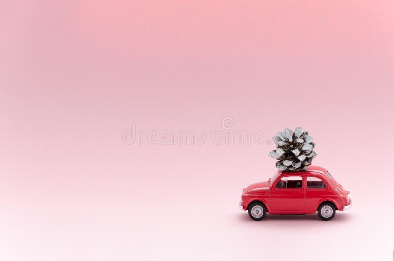 Coche modelo del juguete retro rojo con el cono del pino de la Navidad en fondo rosado la Navidad, concepto de la entrega del inv imagen de archivo libre de regalías