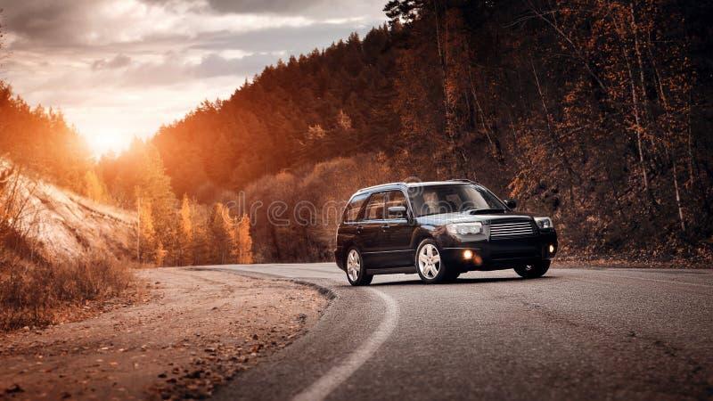 Coche negro en la carretera de asfalto en la puesta del sol fotografía de archivo libre de regalías
