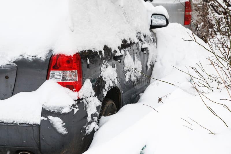 Coche nevado en una nieve acumulada por la ventisca en un aparcamiento fotos de archivo