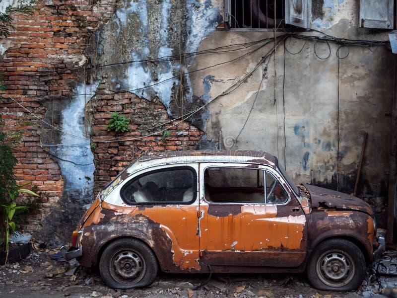 Coche oxidado abandonado viejo en viejo fondo de la pared de ladrillo imagen de archivo libre de regalías
