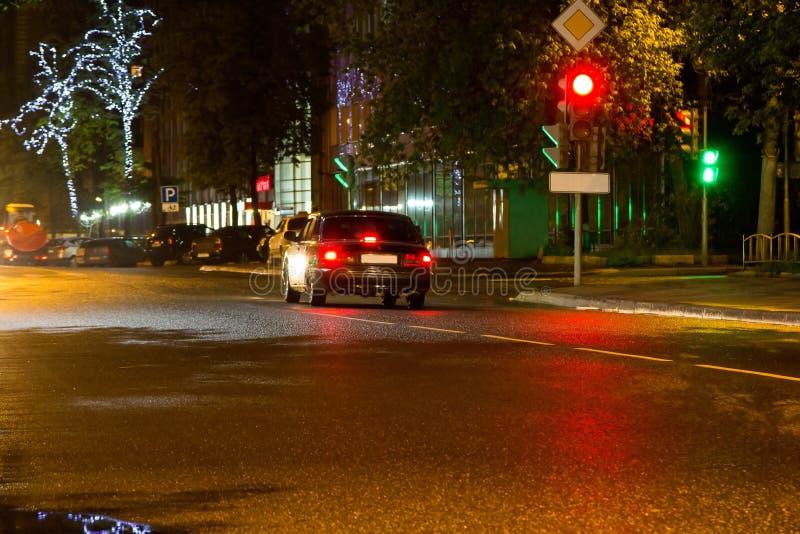 Coche parado en el semáforo en la noche imagenes de archivo