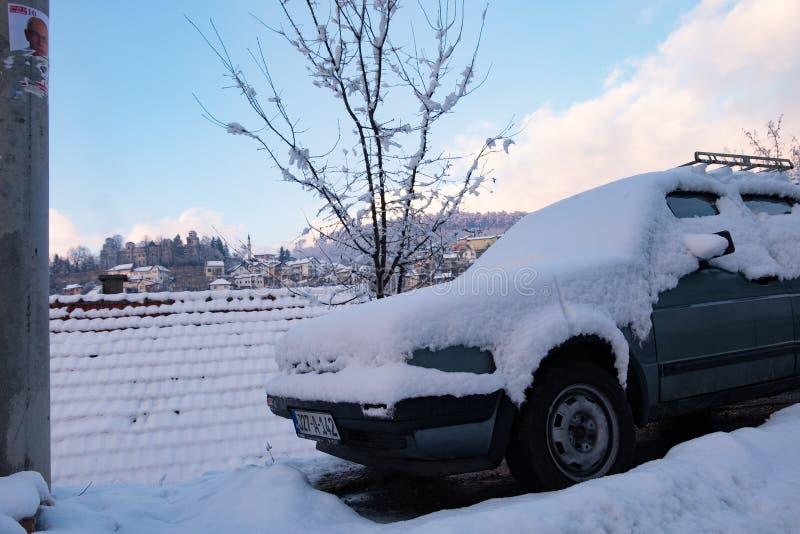 Coche parqueado cubierto por la nieve imagenes de archivo