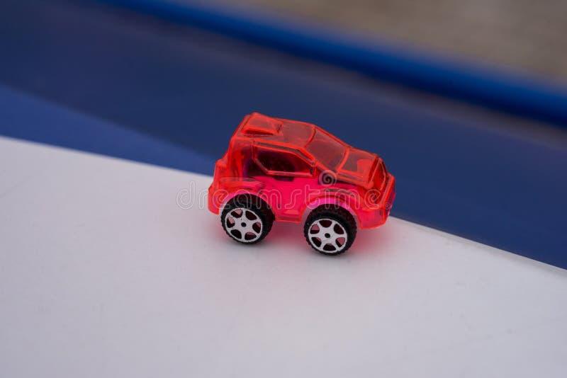 Coche plástico transparente rojo del juguete en fondo azul y blanco imágenes de archivo libres de regalías