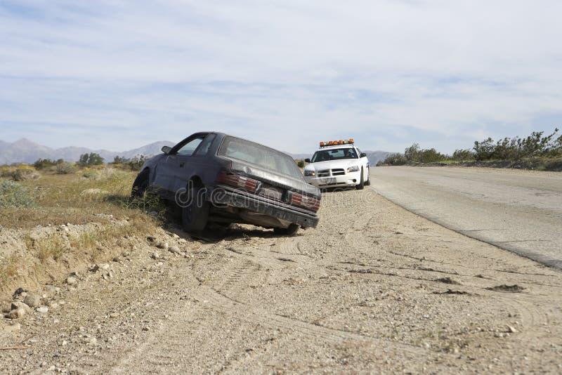 Coche policía con el vehículo abandonado imagen de archivo