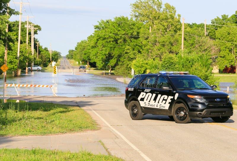 Coche policía en una calle inundada imagen de archivo