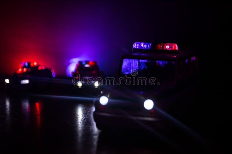 Coche policía que persigue un coche en la noche con el fondo de la niebla Coche policía de 911 respuestas de emergencia que apres fotos de archivo libres de regalías