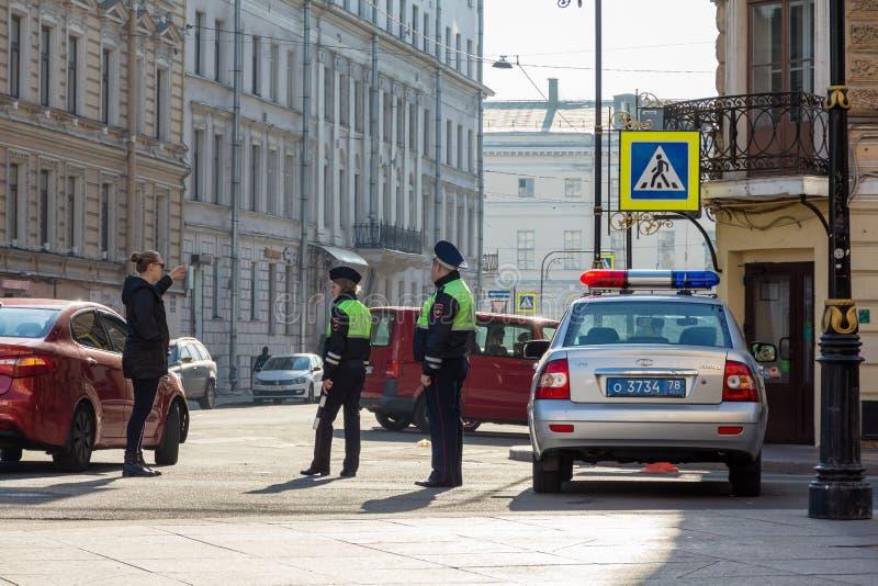 Coche policía ruso de la patrulla y dos polis que hablan con una mujer imagen de archivo