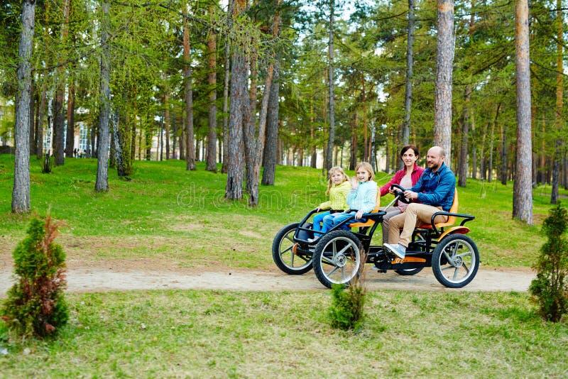 Coche precioso del pedal del quadricycle del montar a caballo de la familia imagenes de archivo