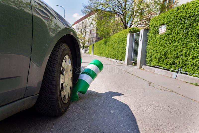 Coche que dobla el poste blanco y verde del tráfico de la seguridad con el parachoques delantero, aparcamiento incorrecto, seguro imagenes de archivo