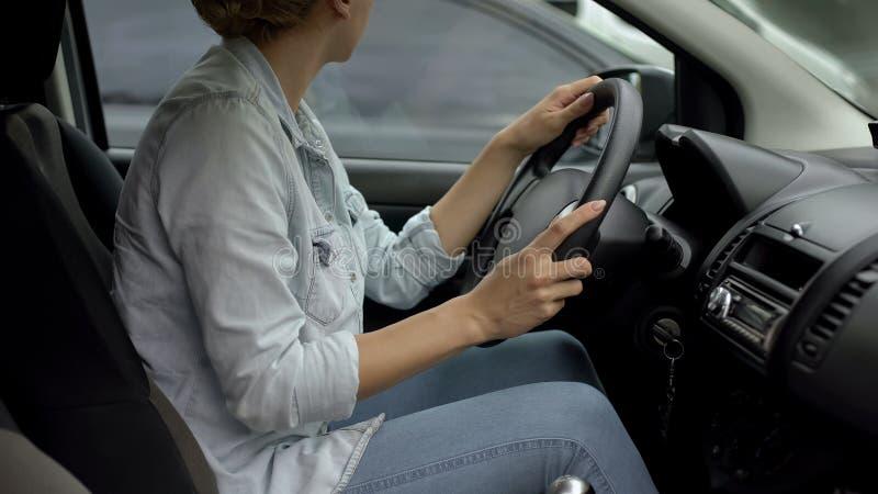Coche que parquea del conductor femenino rubio, falta de experiencia del en-camino, regulaciones de tráfico imagen de archivo