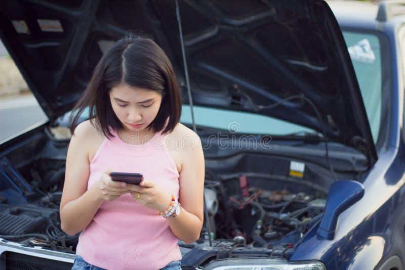 Coche quebrado que hace una pausa de la mujer joven en el camino y el smartphone con que llaman ayuda fotos de archivo