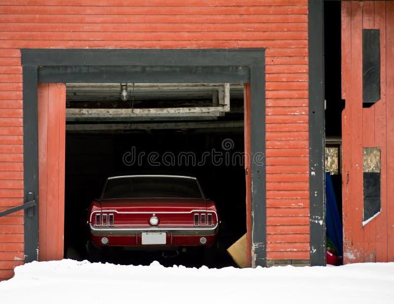Coche rojo clásico en granero imagenes de archivo