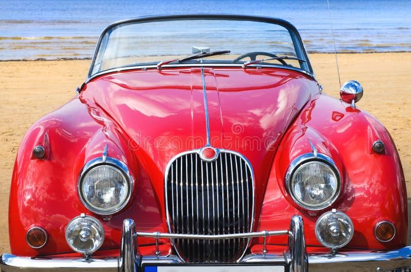 Coche rojo clásico viejo en la playa imagen de archivo