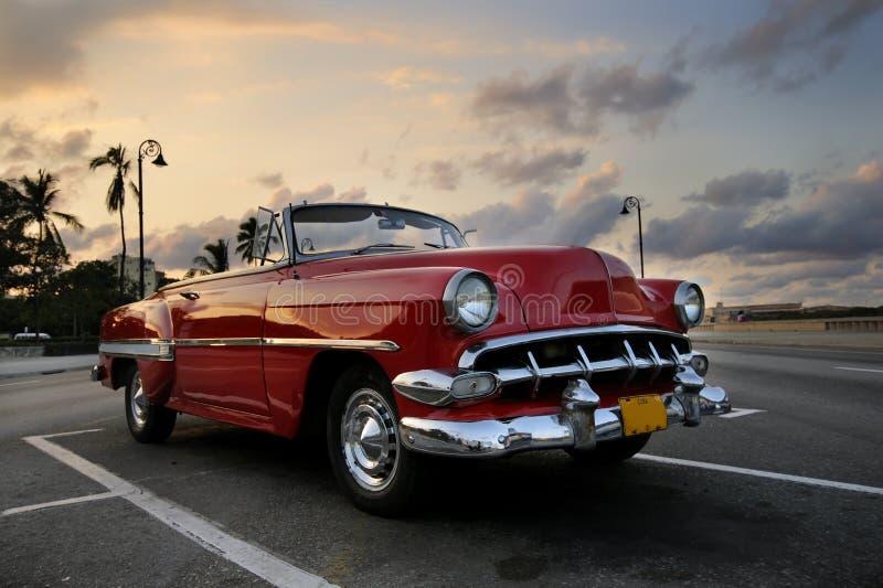 Coche rojo en la puesta del sol de La Habana fotos de archivo