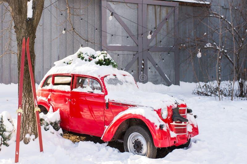 Coche rojo viejo con las ramas de árbol de navidad en el tejado en la yarda nevada foto de archivo