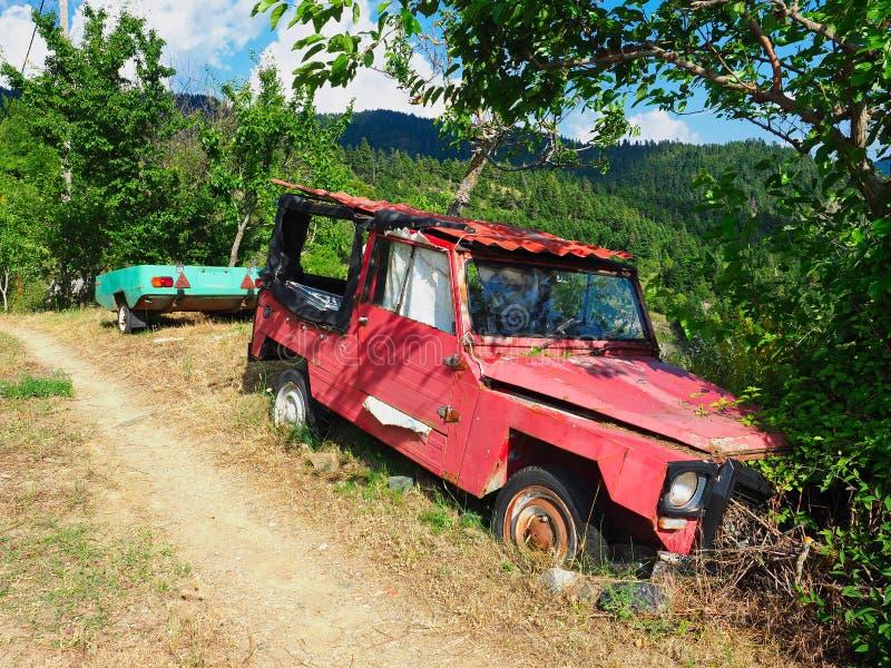 Coche rojo viejo y remolque verde abandonados en zona rural fotografía de archivo libre de regalías