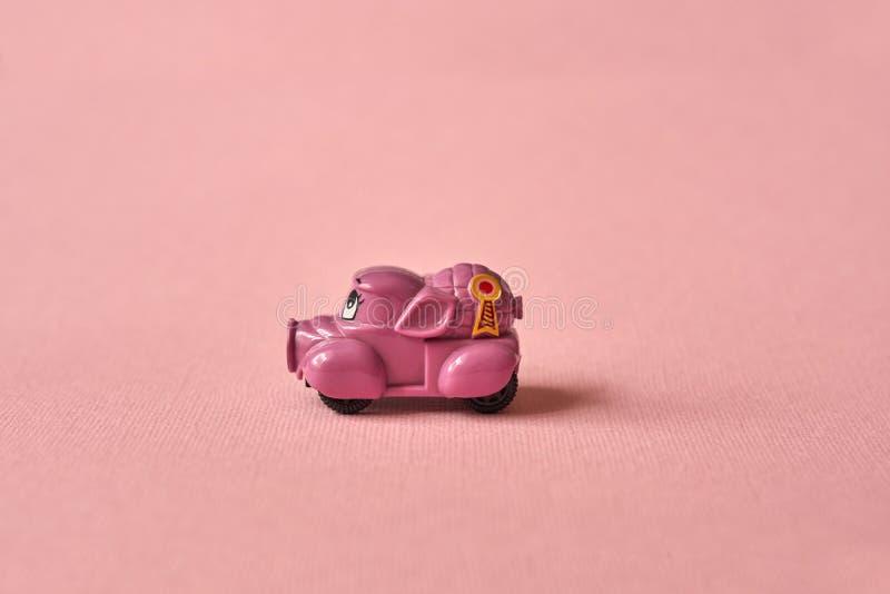 Coche rosado del juguete que entrega productos en un fondo rosado Postal 14 de febrero, el día de tarjeta del día de San Valentín foto de archivo