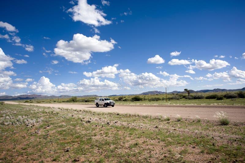 Coche solo en un camino del graveld en Namibia imagenes de archivo