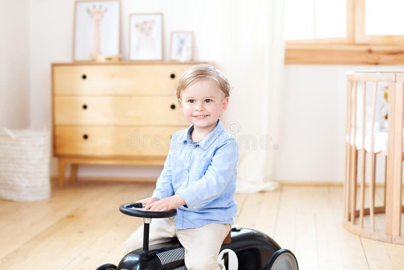 Coche sonriente del vintage del juguete del montar a caballo del niño del retrato Ni?o divertido que juega en casa Vacaciones de  foto de archivo