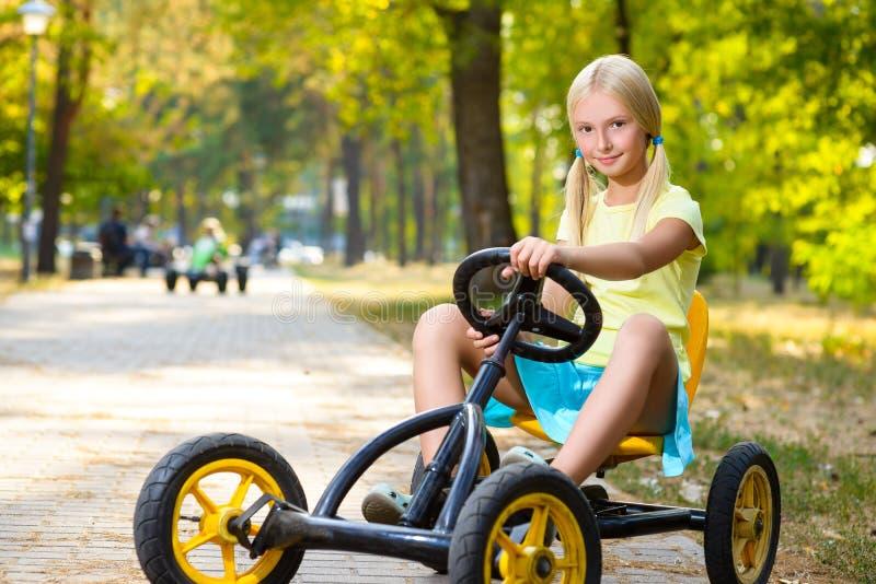 Coche sonriente hermoso del juguete del montar a caballo de la niña adentro foto de archivo