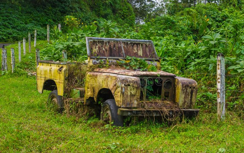 Coche viejo y aherrumbrado abandonado que decae en el medio de la selva tropical verde en Volcan Arenal en Costa Rica imagen de archivo libre de regalías