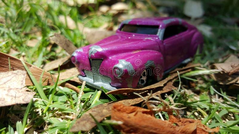 Coche violeta minúsculo del juguete en el parque imagenes de archivo
