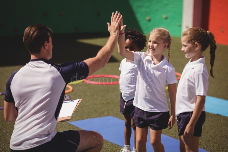 Coche y alumnos que dan el alto cinco el uno al otro fotografía de archivo