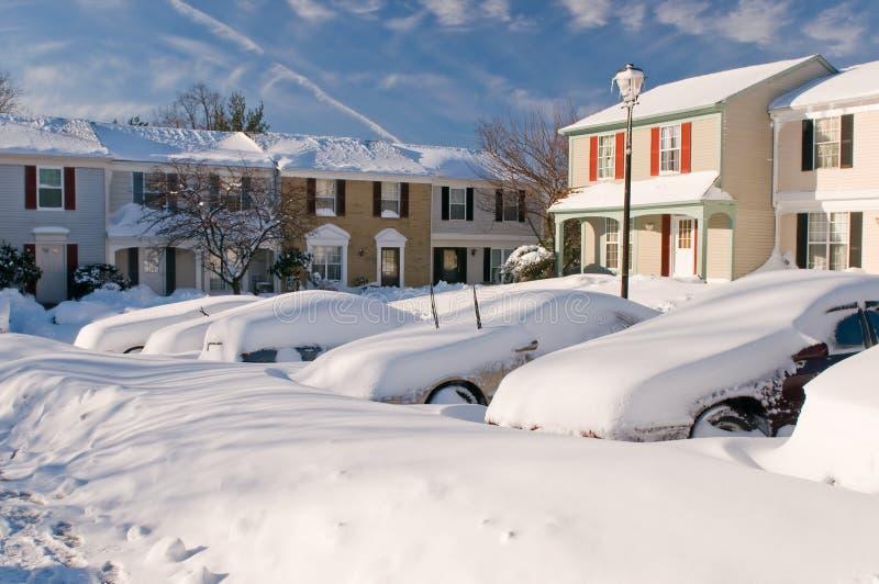Coche y casas después de la tempestad de nieve fotos de archivo