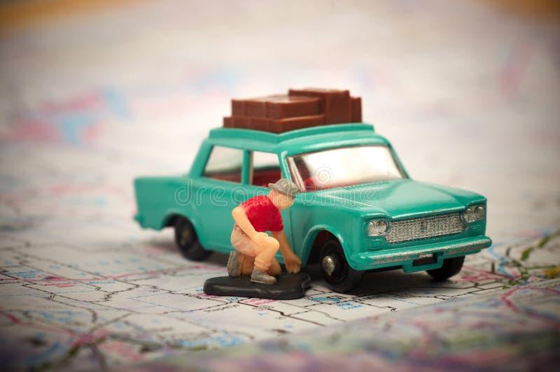 Coche y hombre del juguete que comprueban el neumático imagen de archivo