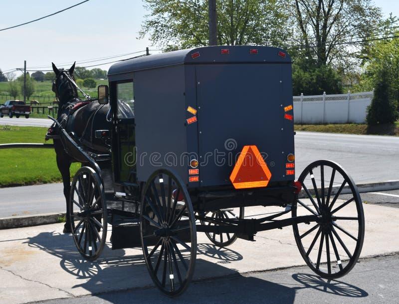Cochecillo traído por caballo de Amish parqueado en una tienda fotografía de archivo