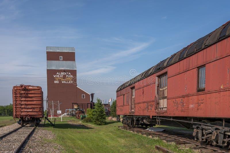 Coches de tren viejos y un elevador de grano en valle grande imagen de archivo