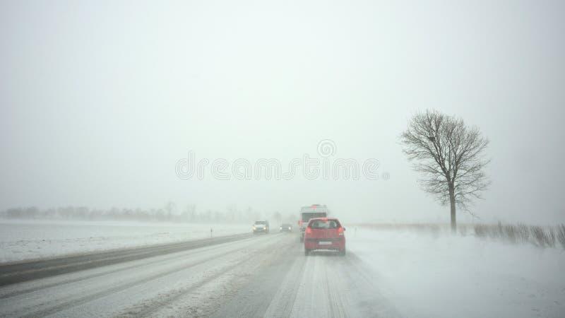 Coches en la carretera por la nevada imagen de archivo libre de regalías
