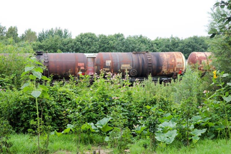Coches espaciosos cilíndricos oxidados sucios de los coches del tanque del ferrocarril del metal del hierro para un tren en un fe imágenes de archivo libres de regalías