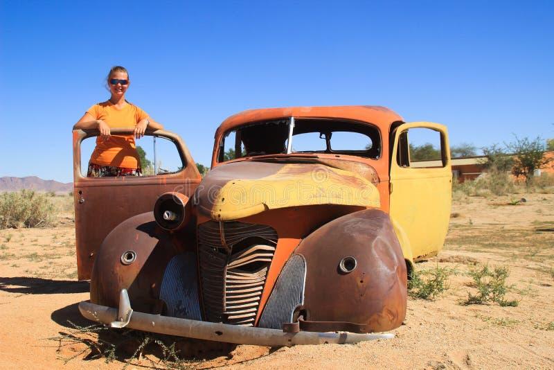 Coches oxidados viejos abandonados en el desierto de Namibia y una muchacha turística blanca regordeta cerca del parque nacional  imagen de archivo libre de regalías