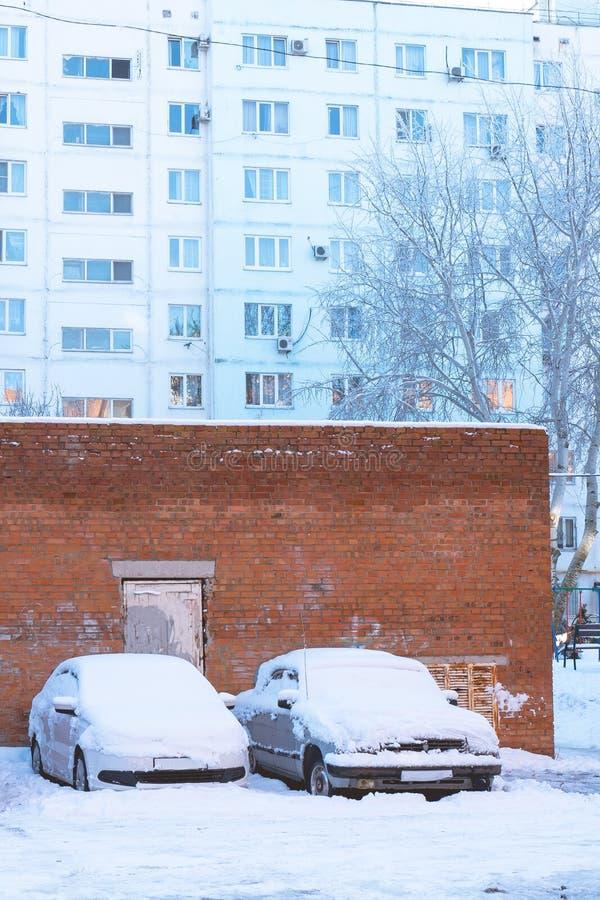 Coches parqueados cubiertos con nieve en el fondo de la casa fotos de archivo libres de regalías