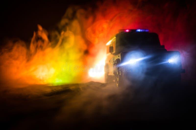 Coches polic?a en la noche Coche polic?a que persigue un coche en la noche con el fondo de la niebla Respuesta de emergencia 911 imagen de archivo libre de regalías