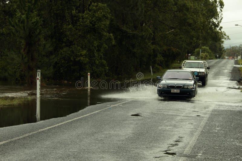 Coches que cruzan el camino inundado imagenes de archivo