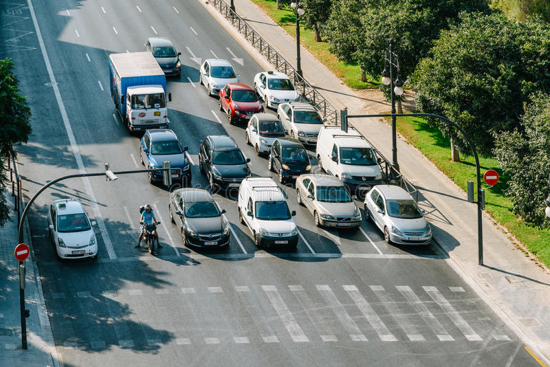 Coches que esperan en el semáforo peatones para cruzar la calle fotografía de archivo