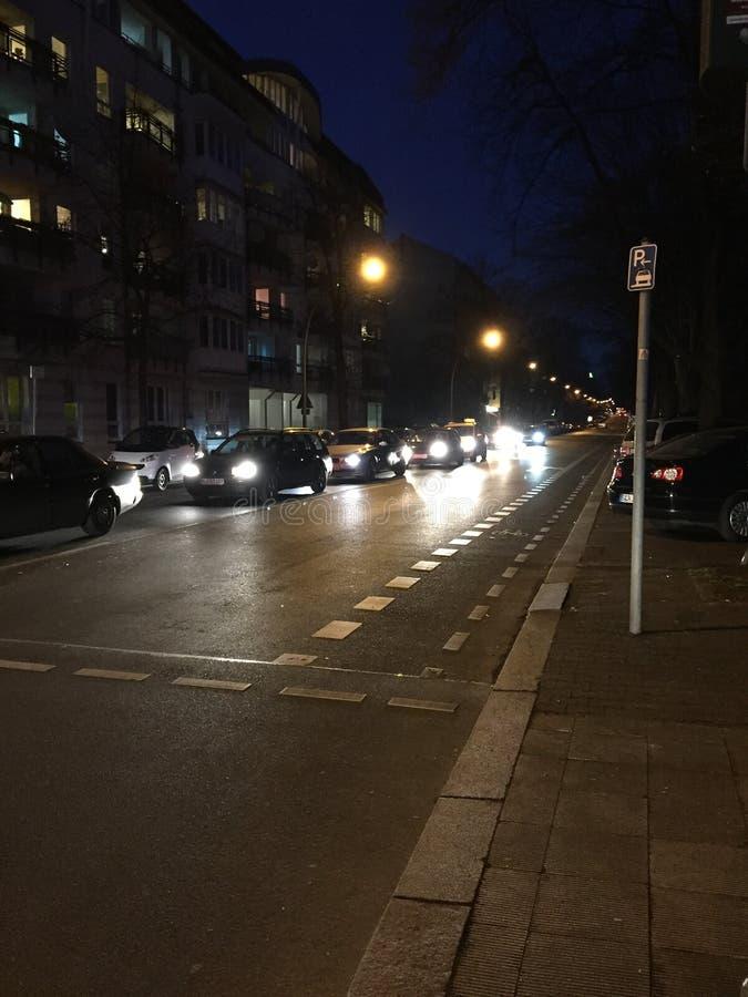 Coches que esperan la luz en la noche en la calle imágenes de archivo libres de regalías