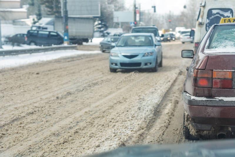 Coches que mueven encendido la calle de la ciudad en el camino nevoso resbaladizo en invierno Vehículos cubiertos con la deriva d foto de archivo libre de regalías