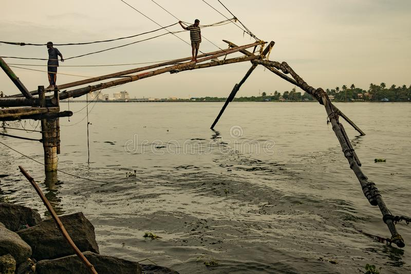 Cochin, India - 20 august 2019: fishermen stand on traditional chinese fishing nets in early morning with warm natural soft light. Cochin, India - 20 august 2019 royalty free stock photography