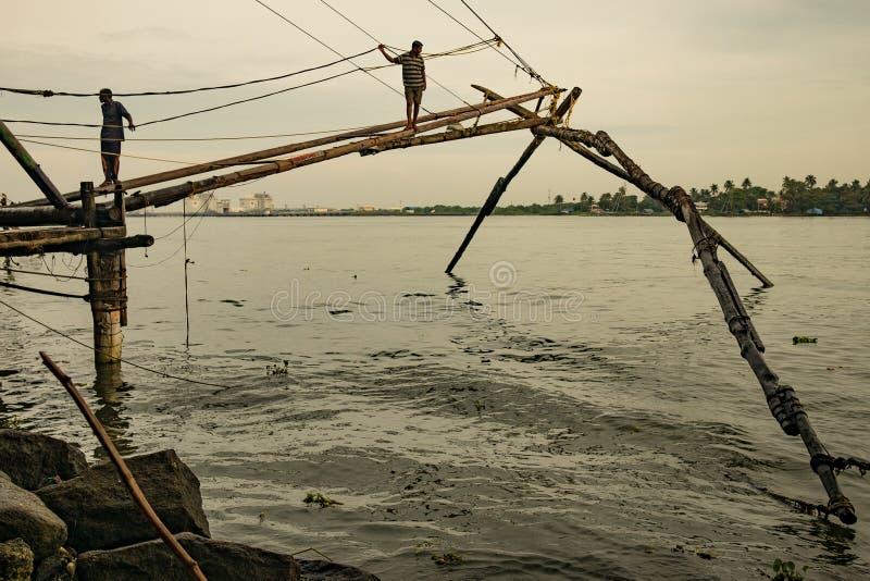 Cochin, Indien, 20 augusti 2019: Fiskarna står på traditionella kinesiska fiskenät tidigt på morgonen med varmt naturligt lätt lj royaltyfri fotografi