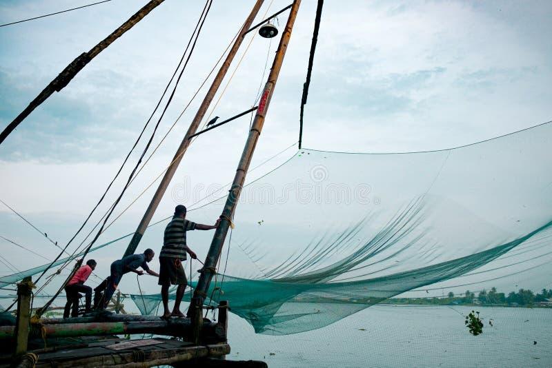 Cochin, Indien, 20 augusti 2019: Inhemska fiskare står på den traditionella kinesiska strukturen av fiskenät tidigt på morgonen m royaltyfri foto