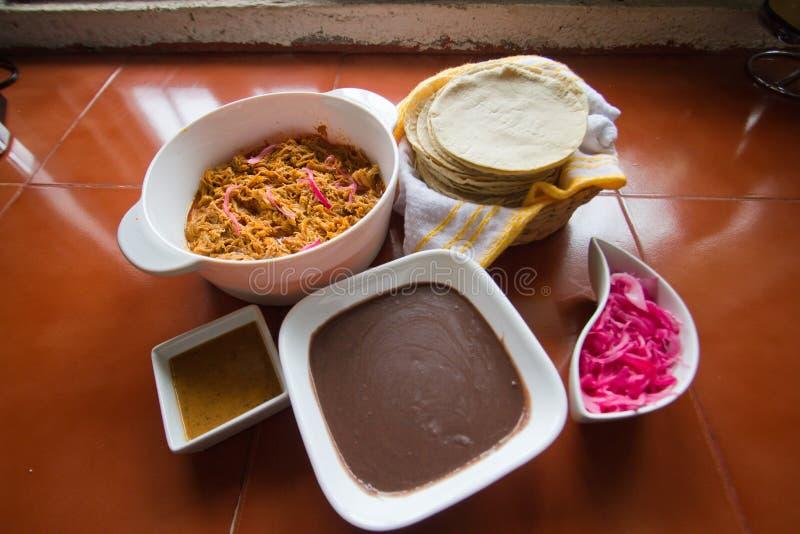 Cochinita Pibil mit schwarzen Bohnen und Tortillas stockbilder