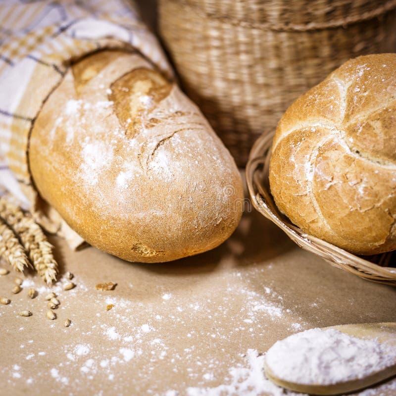 Coció recientemente el pan, el trigo y la harina en un fondo rústico fotos de archivo