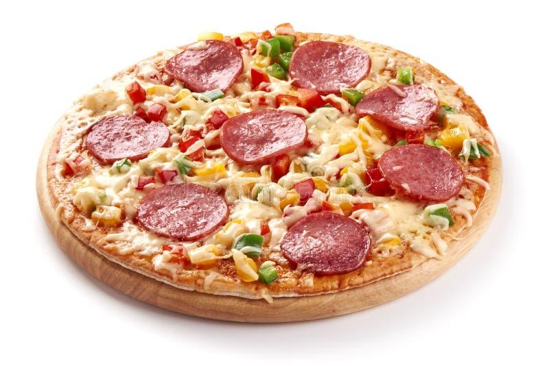Coció recientemente la pizza italiana con el queso y el salami cortado, aislados en el fondo blanco foto de archivo
