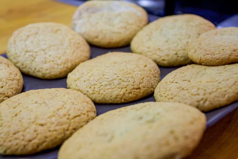 Coció recientemente las galletas de harina de avena hechas en casa cocidas recientemente en un molde para el horno en el papel qu foto de archivo